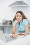Gleeful woman using her laptop smiling at camera Stock Image
