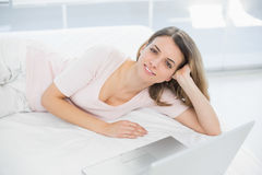 Gleeful young woman posing lying on her bed smiling at camera Royalty Free Stock Photo
