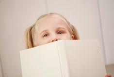 Gleiche eines jungen Mädchens über einem Buch Stockfoto