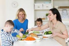 Gleichgeschlechtliche Eltern, die mit Kindern zu Abend essen lizenzfreie stockbilder