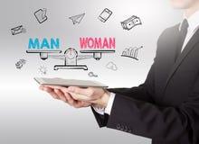 Gleichheit des Mannes und der Frau Junger Mann, der einen Tablet-Computer hält Stockbild