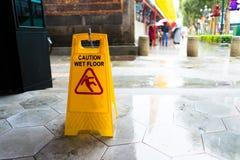 Gleiten Sie Warnzeichen auf dem Bürgersteig an einem regnerischen Tag Lizenzfreie Stockfotografie