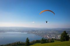Gleitschirm über der Zug-Stadt, dem Zugersee und den Schweizer Alpen Stockfoto