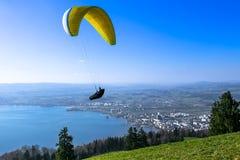 Gleitschirm über der Zug-Stadt, dem Zugersee und den Schweizer Alpen Stockbild