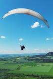 Gleitschirm, der über Berge am Sommertag fliegt Stockfotografie