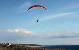 Gleitschirm, der über das Meer gegen den blauen Himmel fliegt Lizenzfreies Stockbild