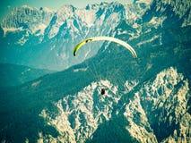 Gleitschirm, der über hohe und schroffe Strecke der Alpenberge fliegt Lizenzfreies Stockbild