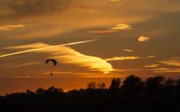 Gleitschirm in einem sonnigen Himmel bei Sonnenuntergang Stockbilder