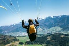 Gleitschirm ist auf den paraplane Streichriemenn - Moment des hochfliegenden Fluges stockfotos