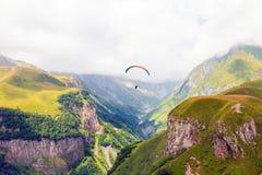 Gleitschirme, die mit paramotors mit schönem Bergblick gegen blauen bewölkten Himmel fliegen stockfotos