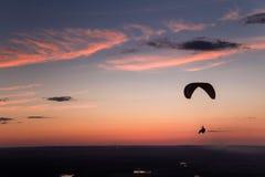 Gleitschirmfliegen auf dem Sonnenuntergang Stockbild