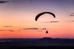 Gleitschirmfliegen auf dem Sonnenuntergang Stockbilder