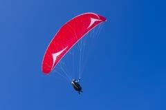 Gleitschirmfliegen im blauen bewölkten Himmel Lizenzfreie Stockfotos