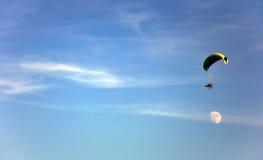 Gleitschirmfliegen im Himmel mit Mond lizenzfreie stockbilder