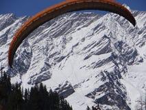 Gleitschirmfliegen und im Hintergrund dort ist ein schöner Schnee umfasste moutains von Indien lizenzfreie stockfotografie