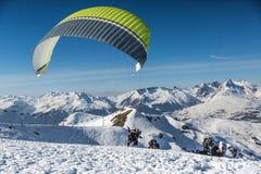 Gleitschirmfliegen von einem Schnee umfasste Gebirgsspitze stockfotografie