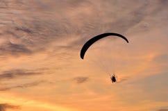 Gleitschirmfliegenfliegen auf dem Himmelsonnenunterganghintergrund Stockbilder