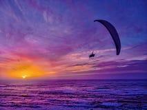 Gleitschirmfliegenflug bei Sonnenuntergang Stockfotografie