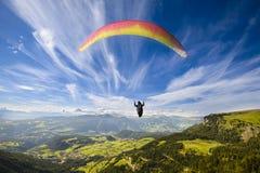 Gleitschirmflugwesen über Bergen Stockbild