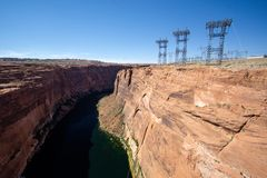 Glen Canyon and Colorado river below the dam with lattice crosses and high voltage power cables. In Arizona stock image