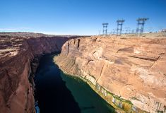 Glen Canyon and Colorado river below the dam with lattice crosses and high voltage power cables. In Arizona royalty free stock image