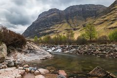 Glencoe river with smooth water flow. And cloudy day. hill views at the back Rural Scene with hill at the background stock images