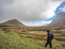 Glencoe Skottland - Maj 18 2017: Mannen fotvandrar till och med regnet i Glencoe, Skottland Fotografering för Bildbyråer