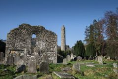 Glendalough Church Ruins and Round Tower. Grave headstones, church ruins and round tower in Glendalough monastic site on Ireland`s east coast stock images