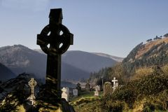Celtic Cross in Glendalough, Ireland. Glendalough is a glacial valley in County Wicklow, Ireland, renowned for an Early Medieval monastic settlement founded in Stock Image
