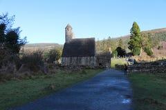 GLENDALOUGH IRLAND - Februari 20 2018: Den forntida kyrkogården i den kloster- platsen Glendalough Berg för Glendalough dal, Wick Royaltyfria Bilder