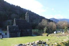GLENDALOUGH IRLAND - Februari 20 2018: Den forntida kyrkogården i den kloster- platsen Glendalough Berg för Glendalough dal, Wick Royaltyfri Bild