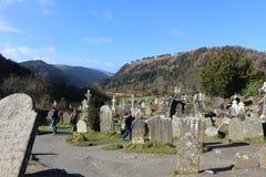 GLENDALOUGH IRLAND - Februari 20 2018: Den forntida kyrkogården i den kloster- platsen Glendalough Berg för Glendalough dal, Wick Arkivfoton