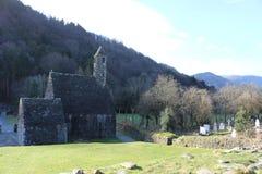 GLENDALOUGH IRLAND - Februari 20 2018: Den forntida kyrkogården i den kloster- platsen Glendalough Berg för Glendalough dal, Wick arkivbilder