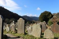 GLENDALOUGH IRLAND - Februari 20 2018: Den forntida kyrkogården i den kloster- platsen Glendalough Berg för Glendalough dal, Wick Royaltyfria Foton