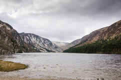 Glendalough Upper Lake with a View of the Wicklow Mountains. The Wicklow Mountains can be seen on the shore of the Upper Lake in Glendalough Royalty Free Stock Photos