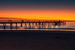 Glenelg-Strand mit den Schattenbildern der Leute an der Dämmerung lizenzfreie stockfotos