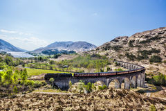 Glenfinnan铁路高架桥在有Jacobite蒸汽火车的苏格兰反对在湖的日落 免版税库存图片