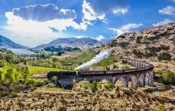 Glenfinnan铁路高架桥在有Jacobite蒸汽火车的苏格兰反对在湖的日落 图库摄影