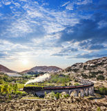 Glenfinnan Railway Viaduct in Scotland with the Jacobite steam train against sunset over lake Royalty Free Stock Photos
