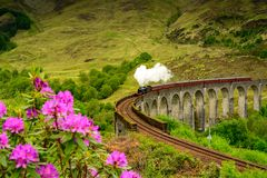 Glenfinnan Railway Viaduct in Scotland with a steam train in the spring time. Glenfinnan Railway Viaduct in Scotland with the Jacobite steam train passing over royalty free stock photos