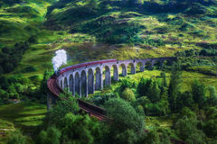 Glenfinnan Railway Viaduct in Scotland with a steam train Royalty Free Stock Photo