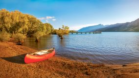 Glenorchy Wharf and pier at golden hour in New Zealand. A canoe on the side of the lake at Glenorchy Wharf with the pier and the mountain range in the distance Stock Photography