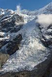 Gletscher, der von den hohen schneebedeckten Bergen fließt Lizenzfreies Stockfoto