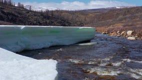 Gletsjer in de lopende rotsachtige bergrivier in de lente stock videobeelden