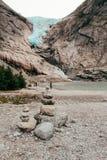 Gletsjer in Noorwegen met opgestapelde stenen in de voorgrond stock afbeelding