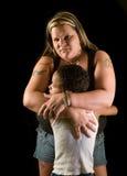 Gli abbracci della madre, protegge il figlio fotografie stock libere da diritti