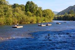 Gli abitanti degli altipiani scozzesi polacchi remano loro barges giù un fiume Fotografia Stock