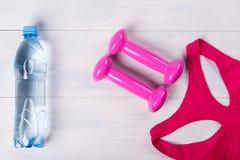 Gli abiti sportivi delle donne, con le teste di legno rosa, su un pavimento di legno leggero e una bottiglia di acqua fotografia stock