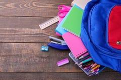 Gli accessori colorati della scuola che cadono da una scuola backpack su una tavola di legno marrone Fotografia Stock