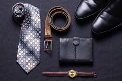 Gli accessori del ` s degli uomini su fondo nero legano lo sho del cinturino di orologio del portafoglio immagine stock